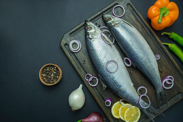 Salted herring with onions and herbs on a cutting board. Dark background. Space for text.